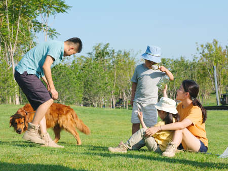 Happy family of four and pet dog playing in the park high quality photo Banque d'images