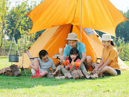 Happy family of four camping outdoors high quality photo