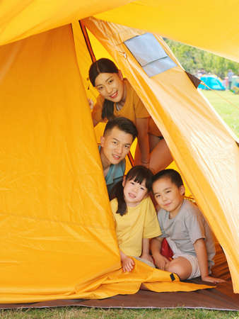 Happy family of four in tent high quality photo