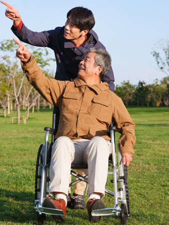 The young man pushed the old man in wheelchair for a walk high quality photo