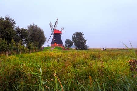 The windmill Wynhamster Kolk on a foggy day Stock Photo