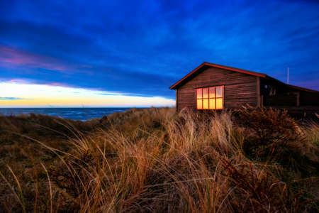 House in the dunes at sunset on a beach near Hirtshals.