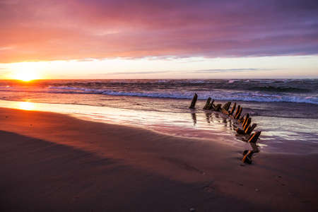 The beach at Hirtshals, Denmark at sunset with an old shipwreck