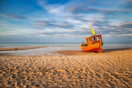 An old, but still used fishing boat at the beach of the village Ahlbeck on the Island Usedom at sunset on a cold day in spring.
