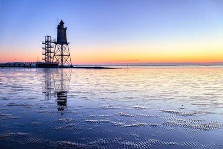 The lighthouse Obereversand near the village Dorum-Neufeld at sunset