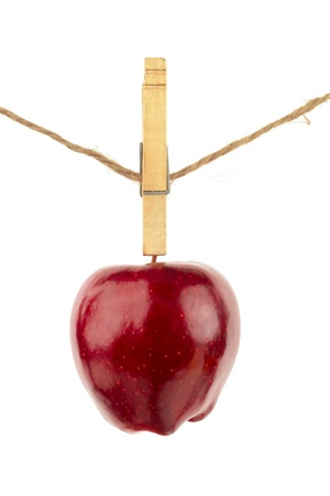 Fresh ripe Red Delicious apple handing from a clothes-pin on twine.