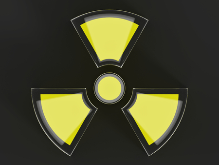 Clear glass black and yellow nuclear symbol isolated on a dark grey background.