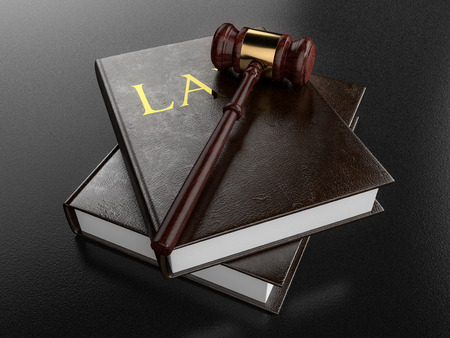 Wooden gavel resting on two law books in front of a dark background. 3D Illustration. Stock Photo