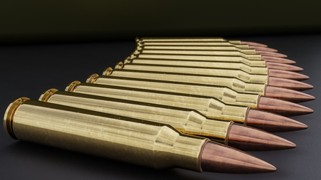 5.56mm assault rifle ammunition spread out on a black granular background.