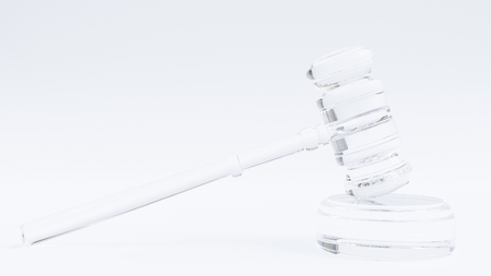 Transparent glass gavel in front of a white background.