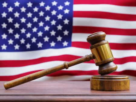 A wooden gavel resting on a judges bench with the American flag in the background. Banco de Imagens - 99339345