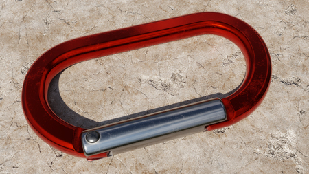 Red aluminium carabiner resting on a rocky background outside.