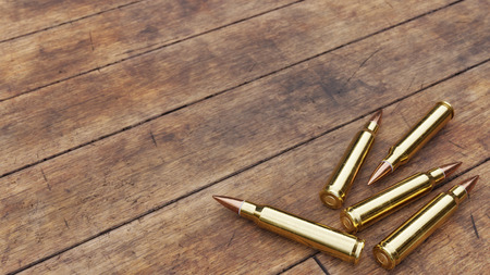 Several rounds of rifle ammunition on aged wooden floor boards.