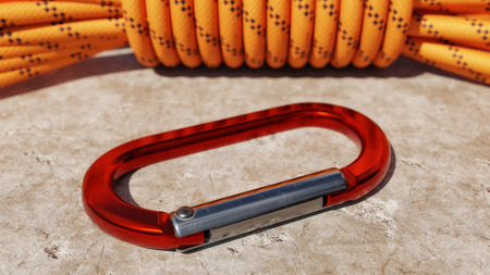 Rope and carabiner resting on a rock background outside