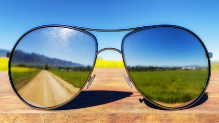 Sunglasses depicting green fields and dirt road on wooden table. 3D Illustration