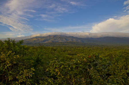 blanketed: Volcano in the distance blanketed by clouds  Stock Photo