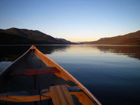 Canoe on calm lake at dusk in Autumn photo