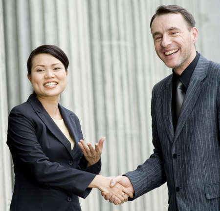 Two business people smiling and shaking hands