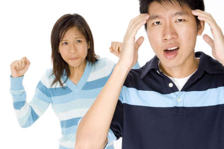 nagging: A man has a headache from relationship stress (woman slightly off-focus behind)