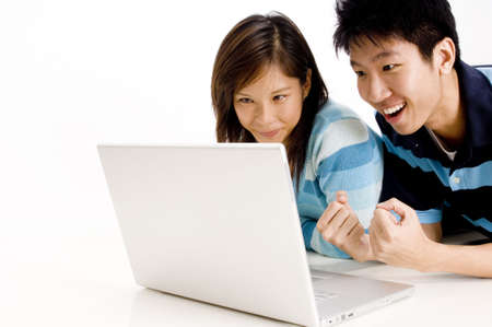 A young man looks excitedly at his laptop as his girlfriend watches