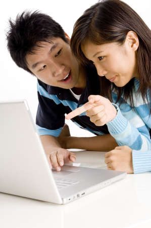 A young couple enjoy using laptop computer on floor