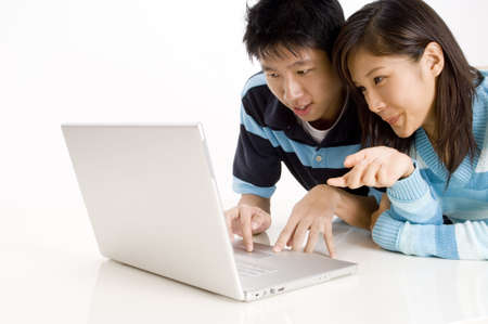 A young couple lying on the floor using a laptop computer