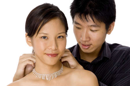 fastens: A young man fastens a necklace around his girlfriends neck