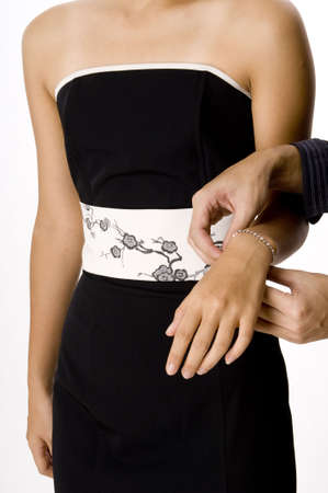 fastens: A man fastens a bracelet around a womans wrist