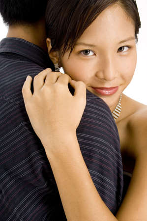 A young pretty asian woman hugs her man photo