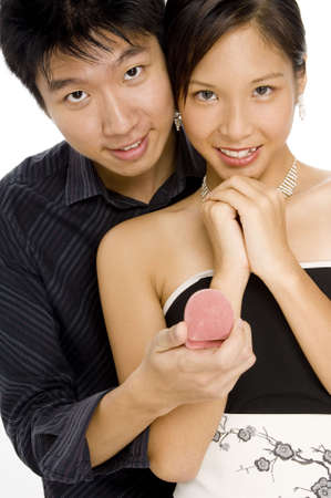 A young woman looks delighted by her mans gift (both looking at camera)