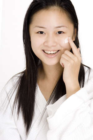 health fair: A young chinese woman applies face cream Stock Photo