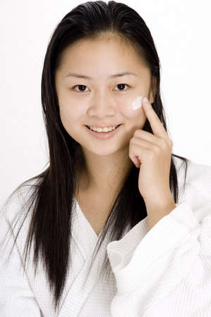 health fair: An asian teenager applying some cream to her cheek