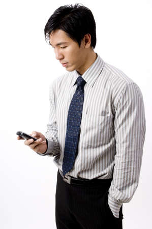 A young asian businessman sends a text message on his phone