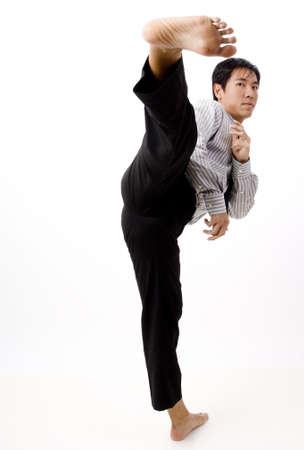 A businessman aims a kick towards the camera photo