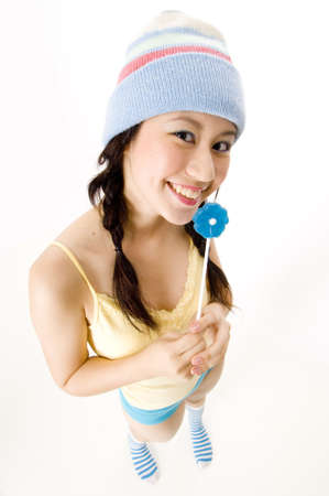 A fun wide-angle shot of a young asian woman in a hat with lollipop photo