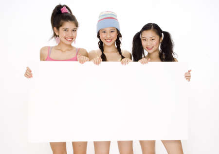 Three young women holding a large blank sign photo