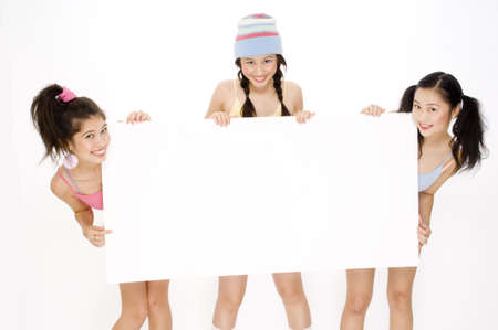 Three pretty teens holding a large blank white sign photo