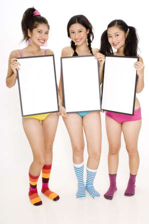 Three pretty teenagers holding signs photo