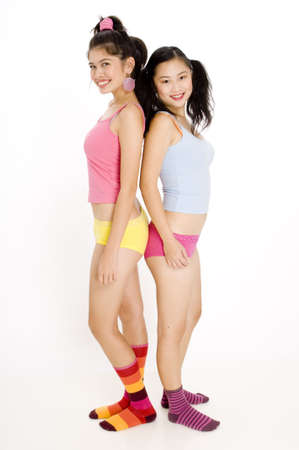 Two young women in colorful clothing on white background photo
