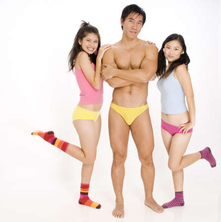 Two pretty young asian women flirt with a muscular guy photo