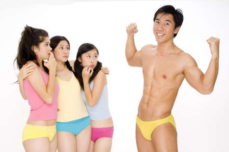 A muscular asian man shows off his physique to three young women photo