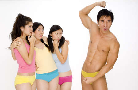 Three young women look shocked as a muscular man hits some poses to impress them photo