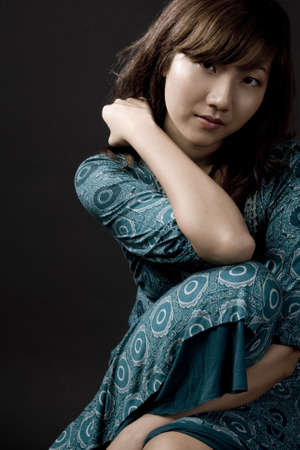 A beautiful young asian woman in a seated pose on black background photo