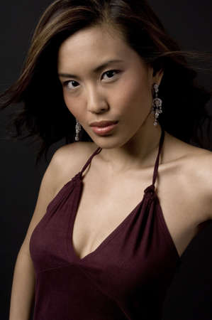 demure: A beautiful young chinese woman in velvet evening dress Stock Photo
