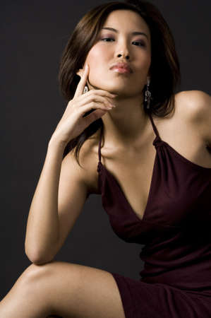 demure: A beautifully poised asian model in an evening dress Stock Photo
