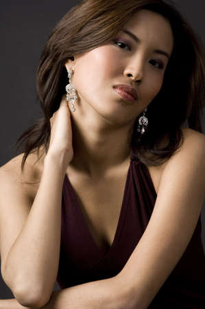 demure: A beautiful asian woman with her hand behind her neck Stock Photo