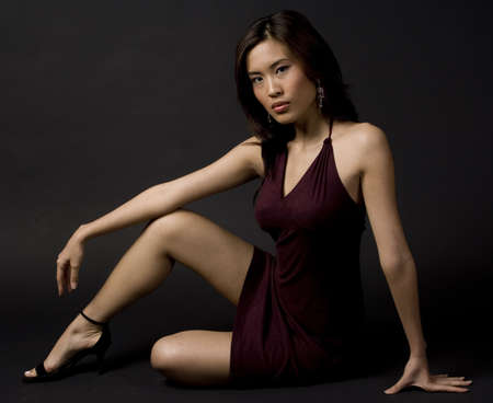 demure: An asian woman sits gracefully on the studio floor on black background Stock Photo