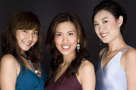 Three attractive young asian women in dresses on black Stock Photo