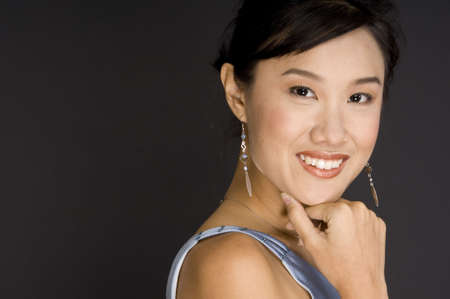 demure: A pretty young asian woman with hand to chin