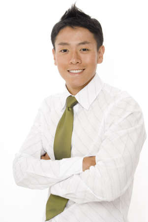 A young asian businessman smiles with arms folded photo
